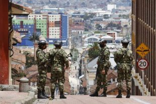 Soldiers patrol a street in Bogotá (Colombia)